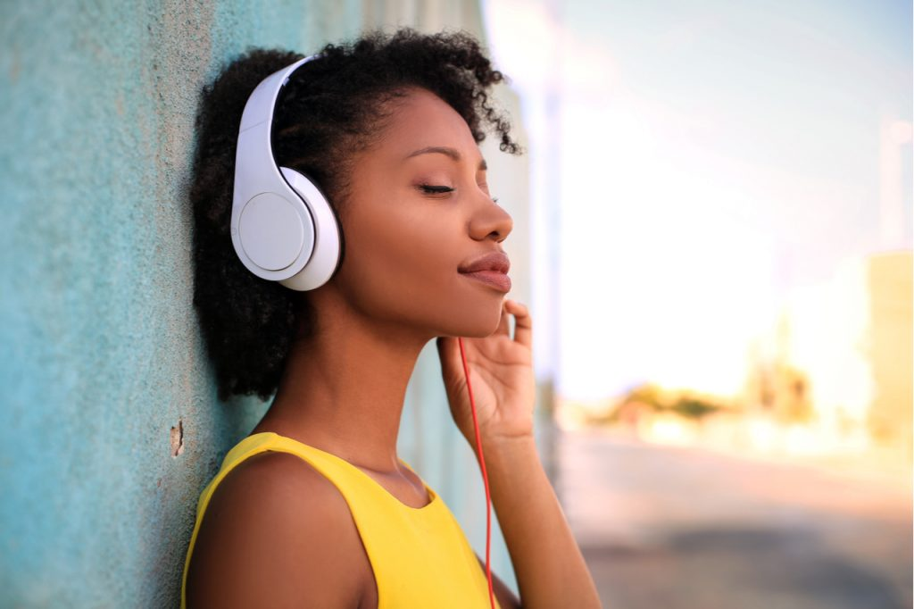 Pretty girl listening music with her headphones in the street.