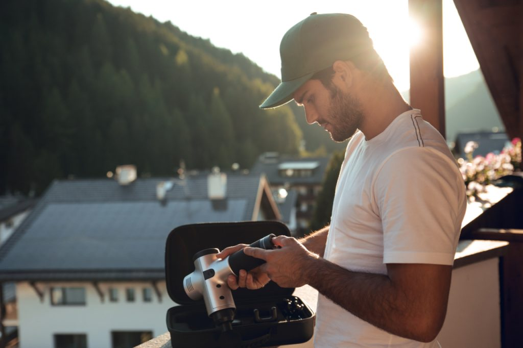 Man with cap and white shirt holding the sonic x massage gun his arm and body at sunset at home.