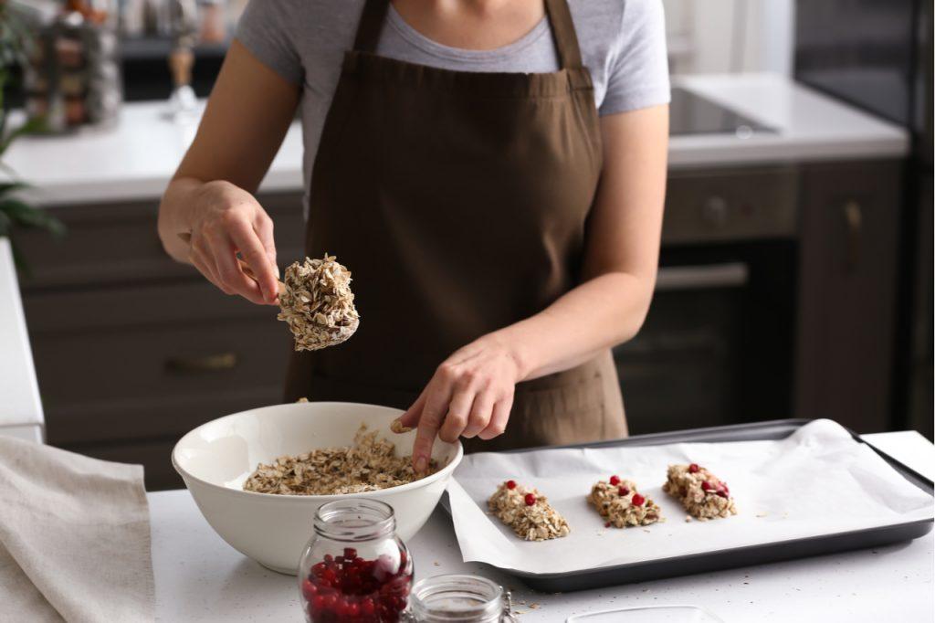 Woman making tasty granola bars in kitchen