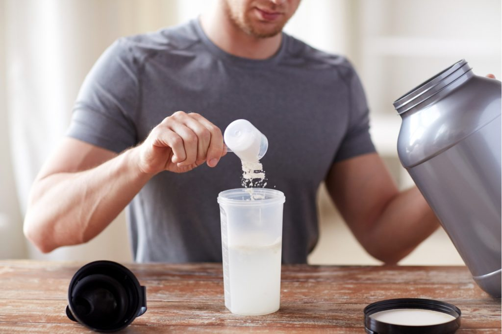 Close up of man with jar and bottle preparing protein shake.
