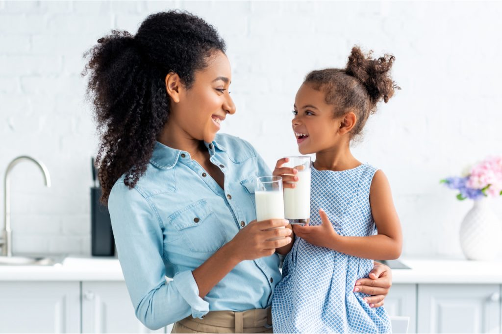 Mother and daughter holding glasses of milk in kitchen and looking at each other.