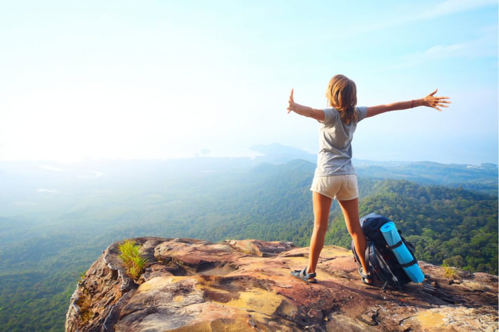Woman with backpack standing on a rock with raised hands and looking to a valley below.