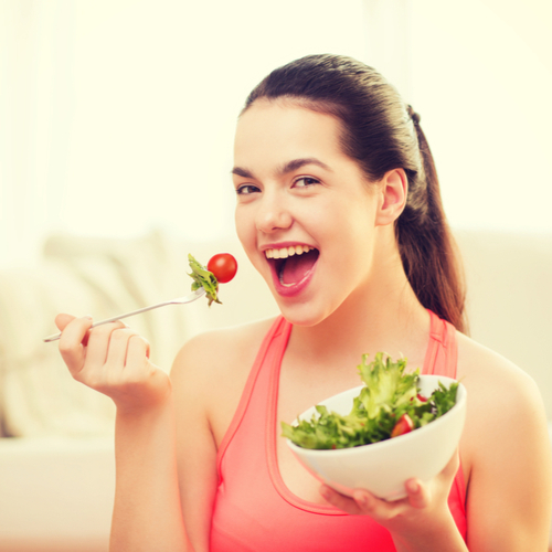 Smiling sporty teenage girl with green salad at home.