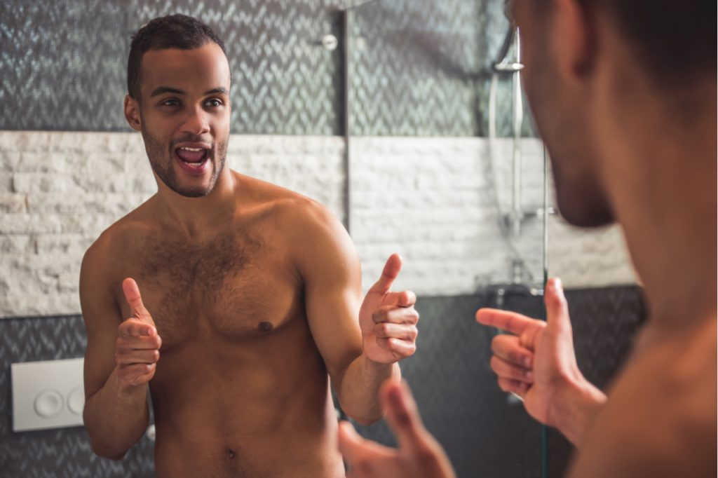Man is winking at himself while looking into the mirror in bathroom.