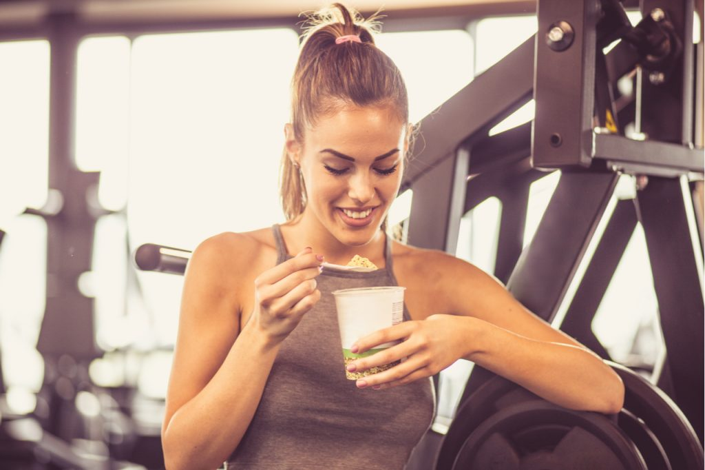 Woman in gym eating pre-workout snack.