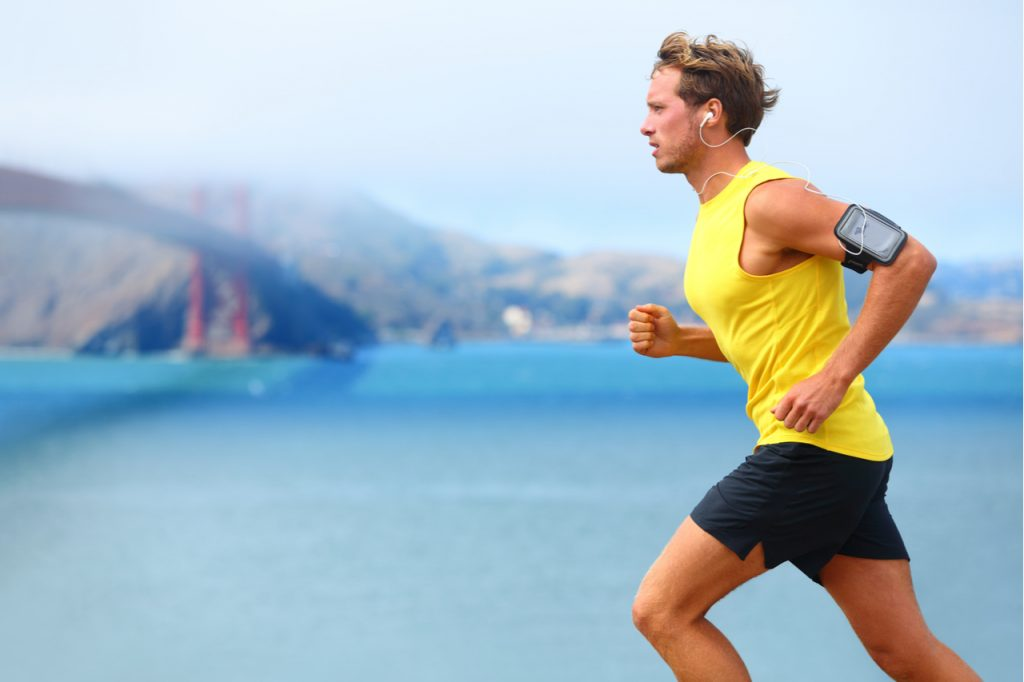 Man jogging near the sea with smart phone armband.