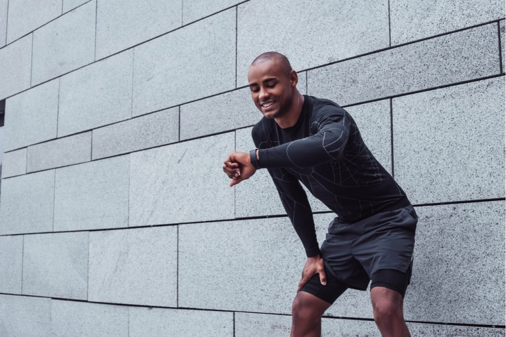 Young man in sportswear looking at his smartwatch with smile while standing against grey background outdoors.