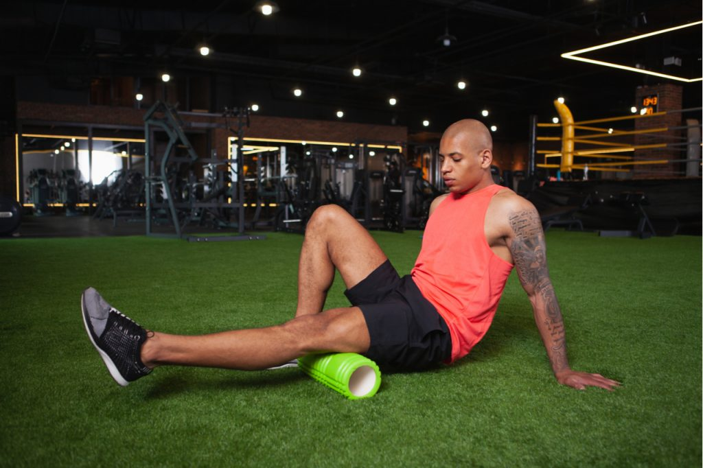 Male athlete relaxing leg muscles after gym workout, using foam roller.