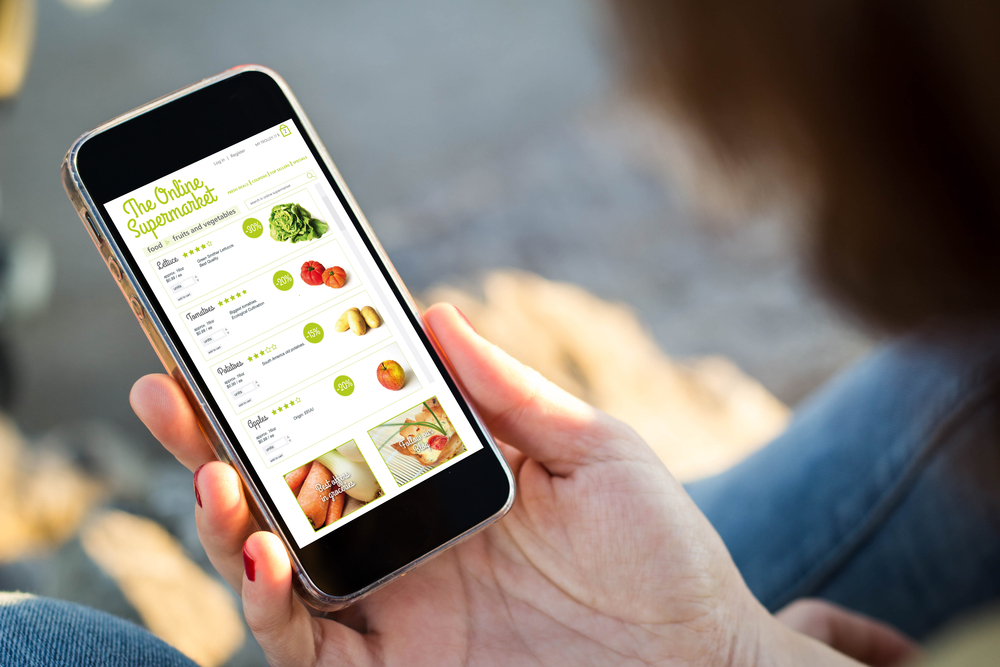 close-up view of young woman shopping groceries on online supermarket with her mobile phone.