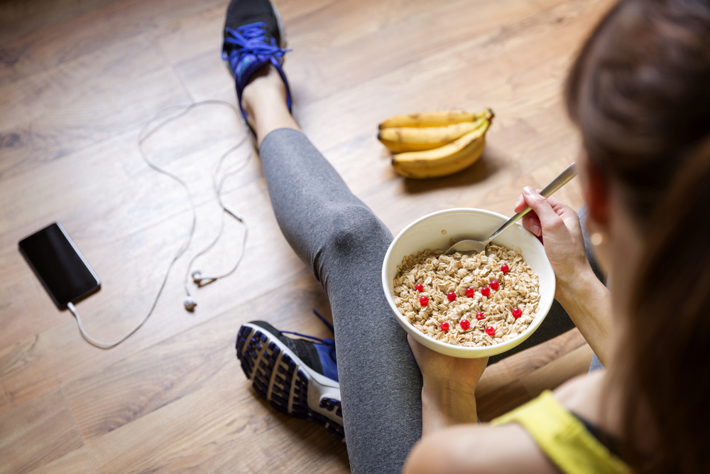 Young girl eating a oatmeal with berries after a workout . Fitness and healthy lifestyle concept.