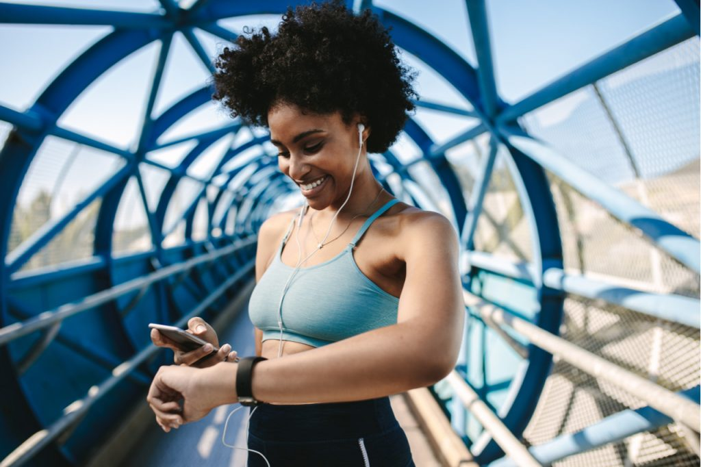 Fit female runner using smart watch and mobile phone to listen to music.