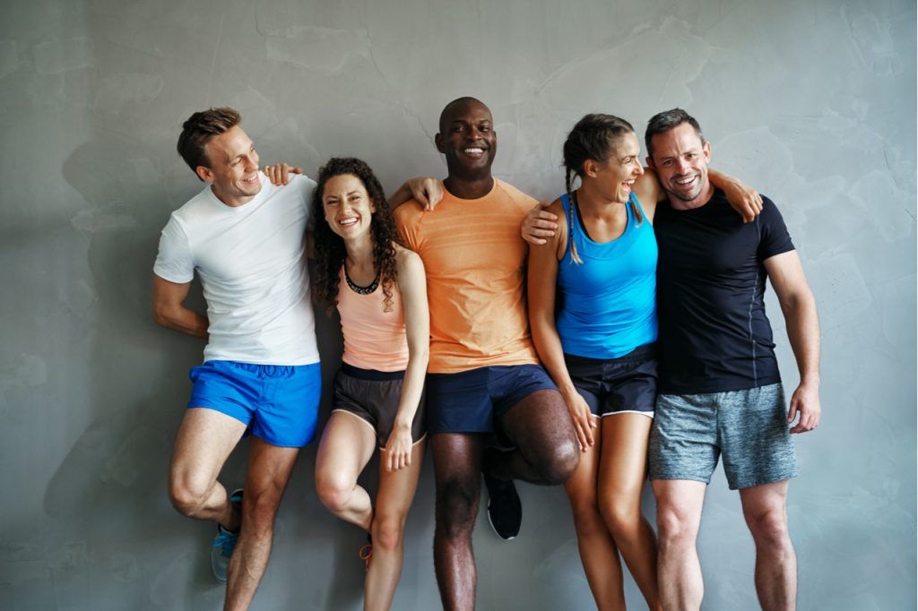 Smiling group of friends in sportswear laughing together with positive mindset while standing arm in arm in a gym after a workout.
