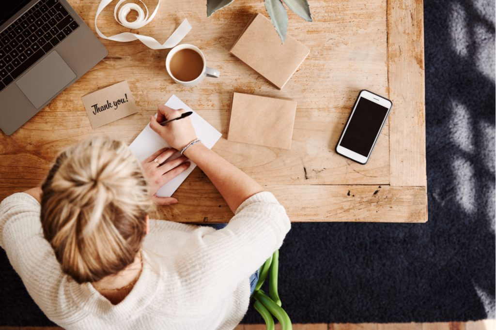 A woman writing thank you notes on her desk while having her coffee in the morning.