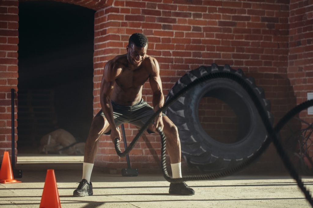 Muscular shirtless man is concentrated on the exercise with battle rope.