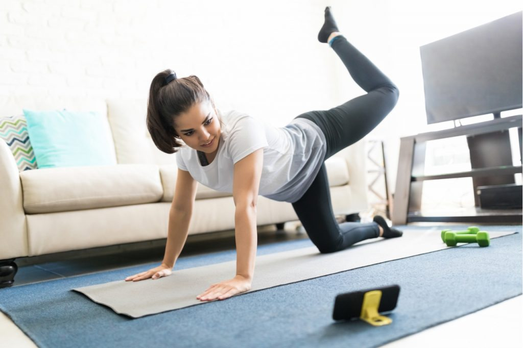 Woman repeating exercises while watching online exercise session on her smart phone at home.
