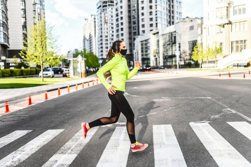 A fit woman doing her morning run with a face mask.
