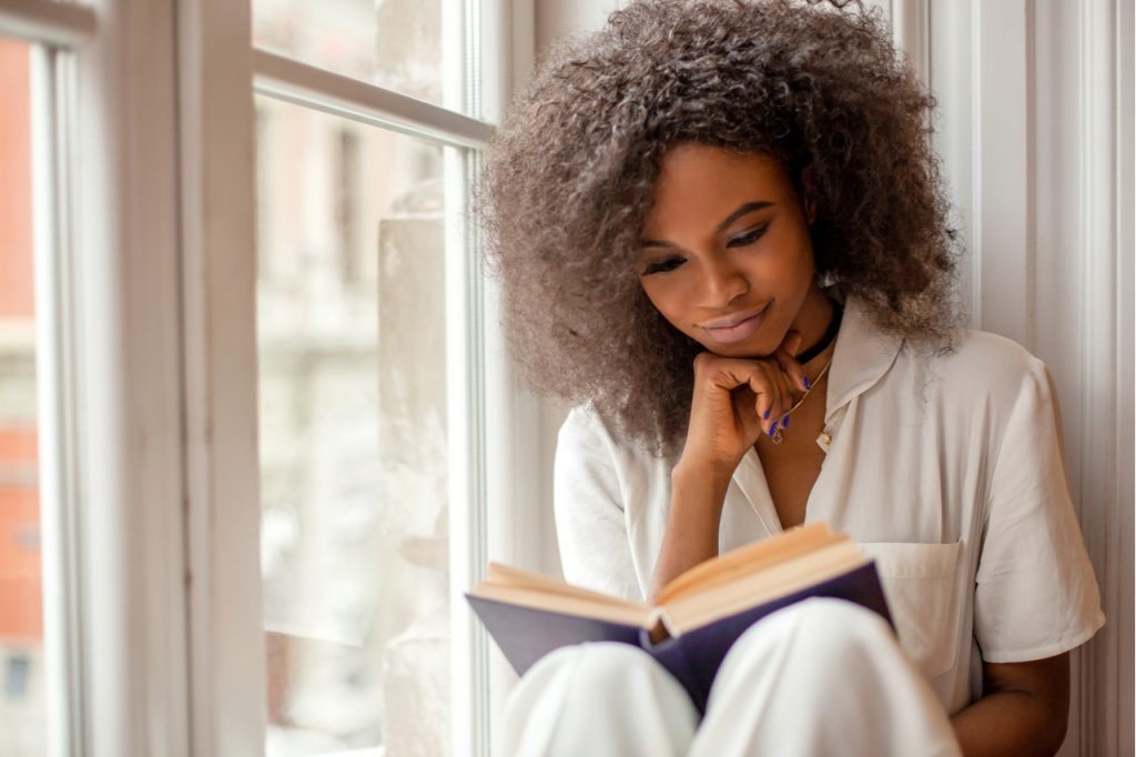 A beautiful african american woman reading a book by the window.