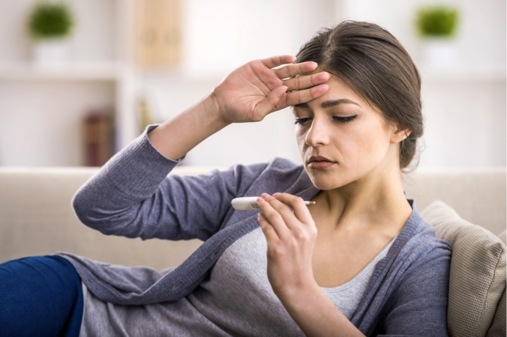 A woman looking at a thermometer while feeling her head for fever.