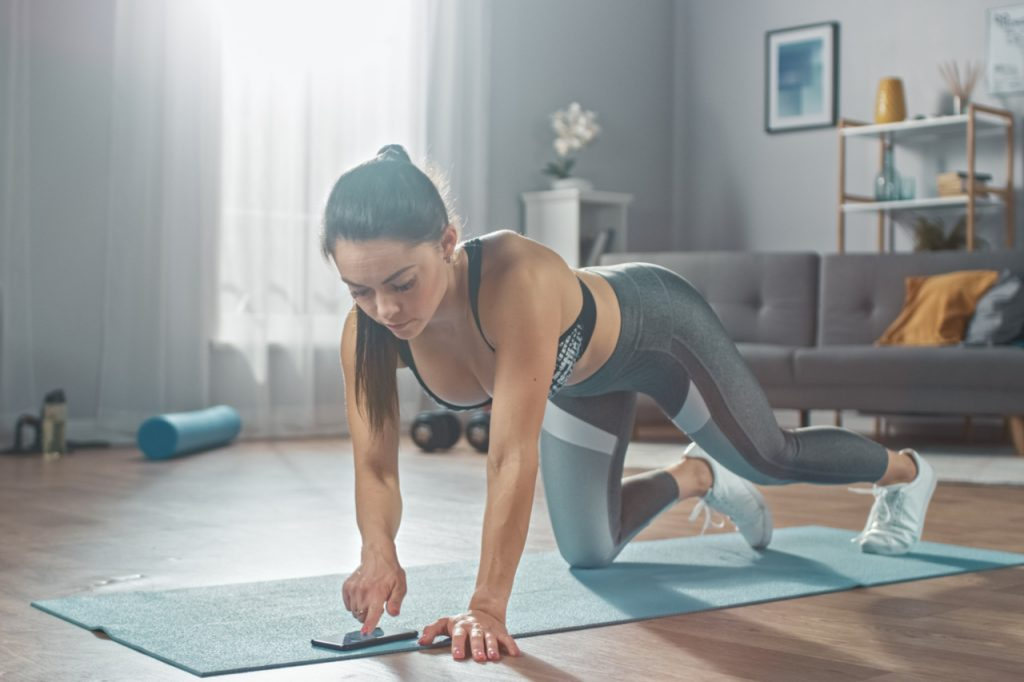 Woman in grey athletic sportswear is doing push up workout exercises while using the best home workout app.