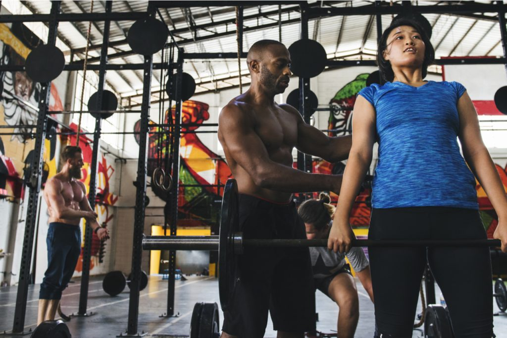 Multiracial people doing workout routine with gym membership.
