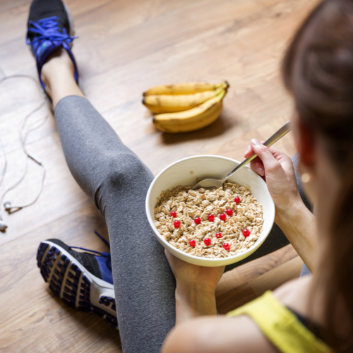 Young girl eating a oatmeal with berries before workout.