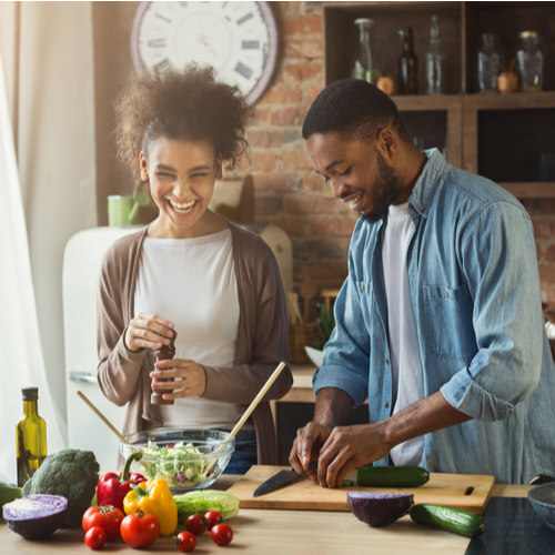 Laughing couple preparing healthy salad together in loft kitchen.