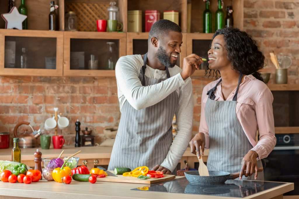 Man feeding his beautiful woman while cooking together at kitchen, empty space.