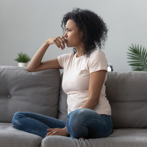 Woman sitting on sofa looking away feel depressed, doubtful, and lonely.