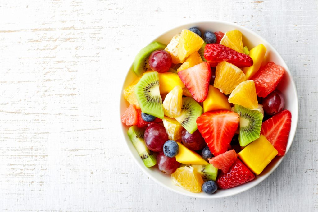 Bowl of healthy fresh fruit salad on wooden background.