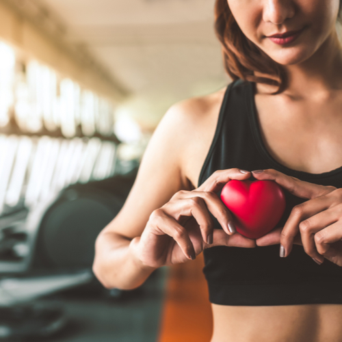 Happy sport woman holding red heart in fitness gym club.