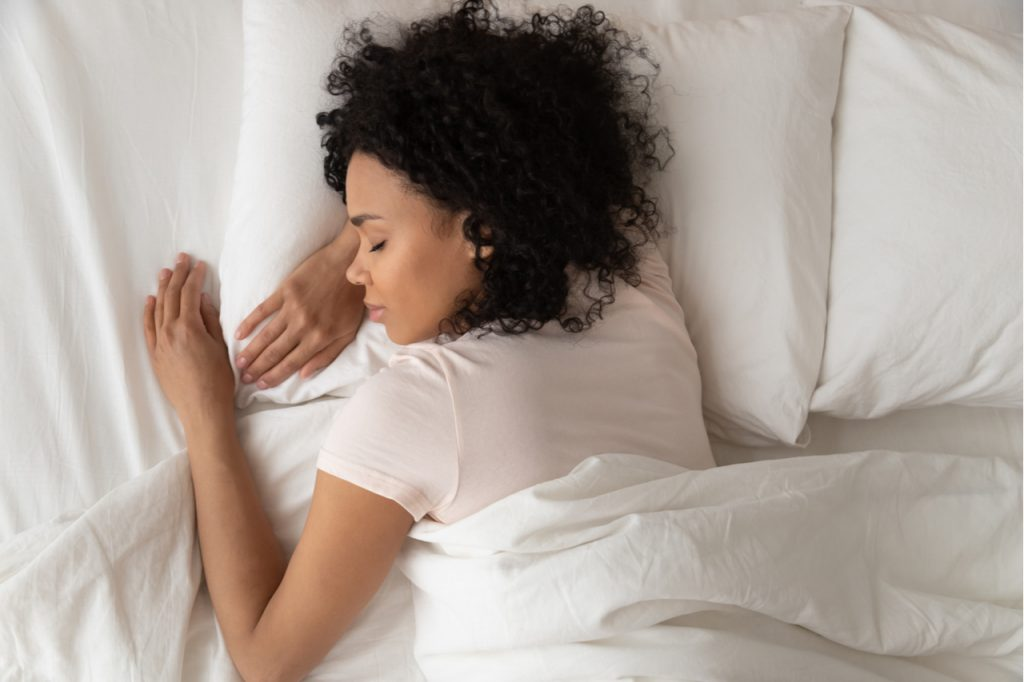 Healthy serene young african american girl sleeping well in comfortable cozy fresh bed