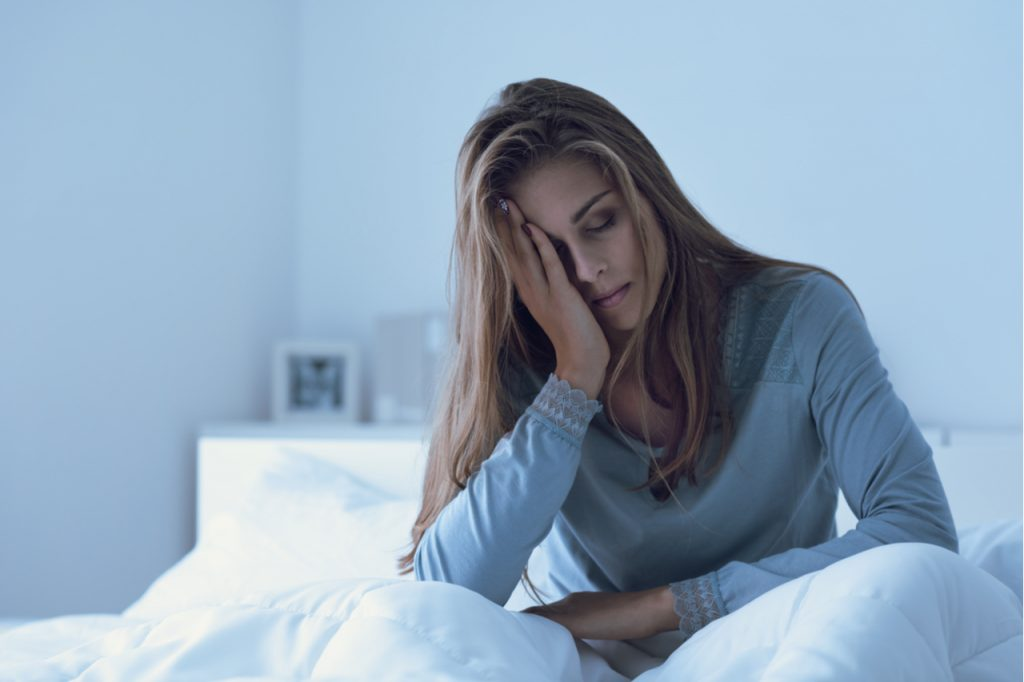 Woman awake in the night, she is touching her forehead and suffering from insomnia which is one of the signs and symptoms of depression.