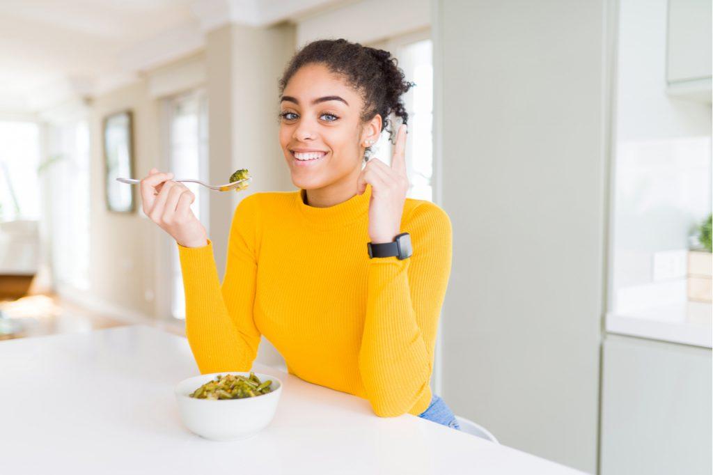 Woman eating healthy green vegatables.