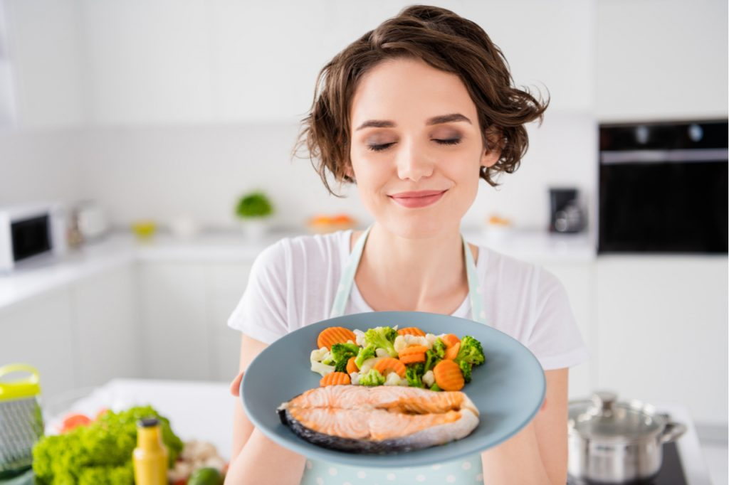 Lady chef hold ready grilled salmon trout fillet steak with garnish cook dinner one person portion eyes closed wear apron t-shirt modern kitchen indoors.
