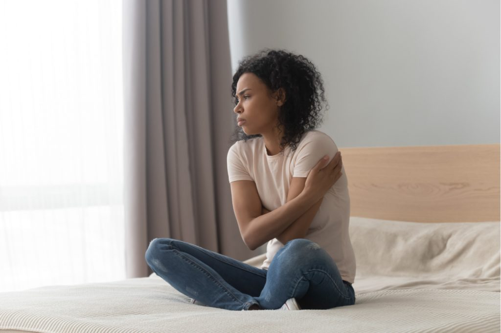 woman sitting in bed alone, hugging herself, feeling lonely.