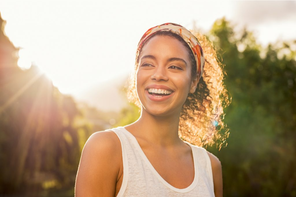 woman smiling and looking away at park during sunset figured how to manage stress.