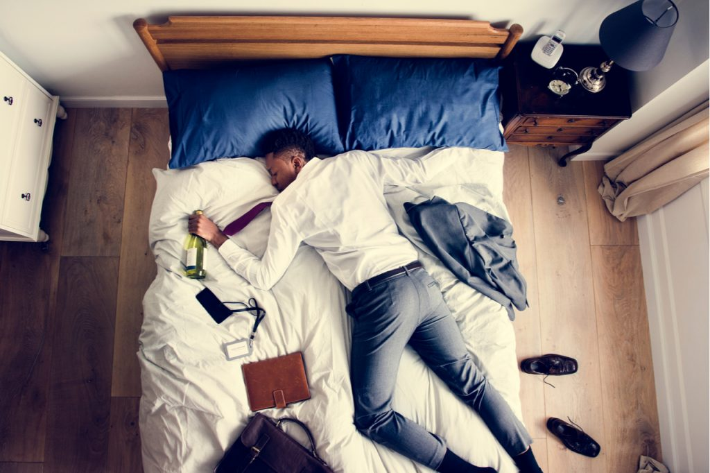 Business man drunk falling asleep as soon as he came back home in need of hangover remedy.