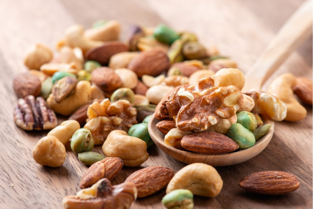 Assorted nuts mix on wooden spoon.
