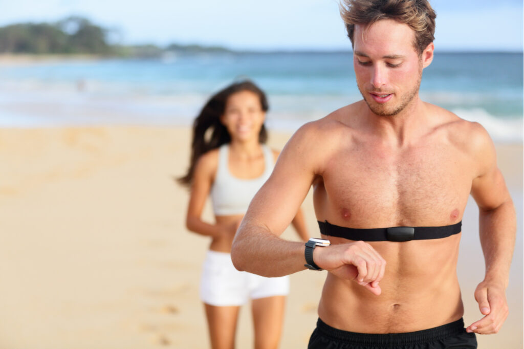 Handsome shirtless male runner working out outside by the ocean wearing heart rate monitor.