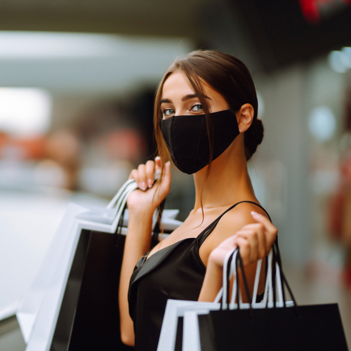 Young woman in protective black medical mask on her face with shopping bags in the mall.