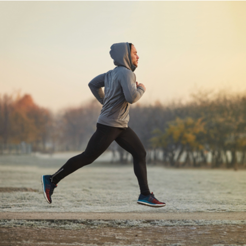 Young athletic man running at park during cold winter morning.