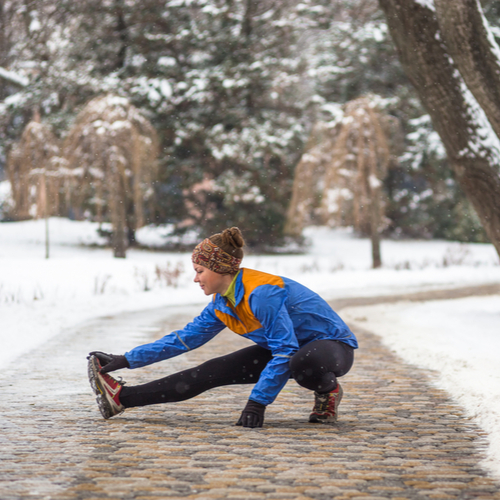 Young sport woman doing exercises during winter.