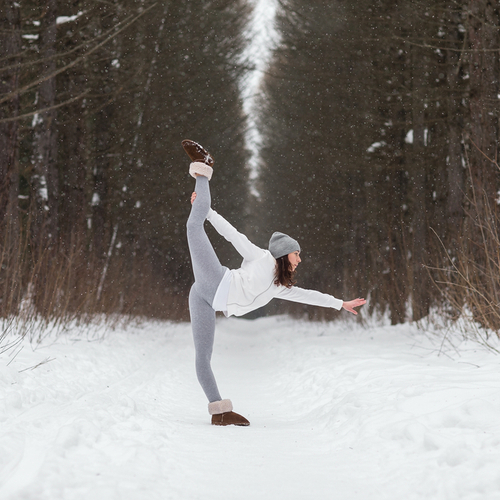 Woman doing yoga in the woods in winter.