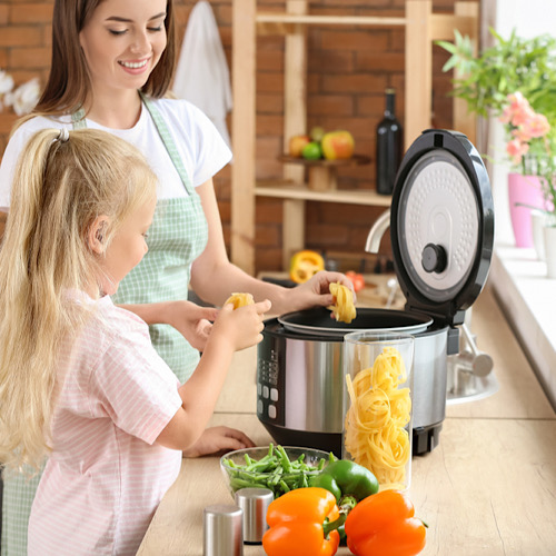 Woman and her little daughter using modern multi cooker in kitchen