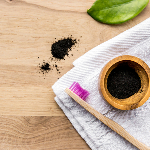 Raw activated charcoal powder in wooden cup and natural bamboo toothbrush next to it, green leaf and bath towel. Charcoal toothpaste concept.