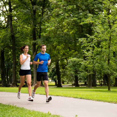 Young man and woman jogging outdoor in nature.