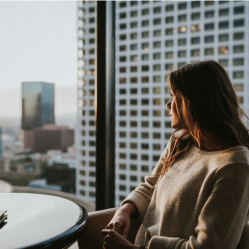 Woman sitting at table enjoying the city skyline at sunset with stunning panoramic view.