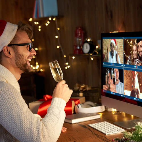Happy young man wears santa hat drinking champagne talking meeting friends on virtual zoom video call celebrate holiday.