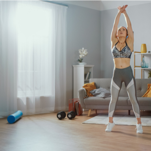Woman doing stretching in her living room with gym equipments.