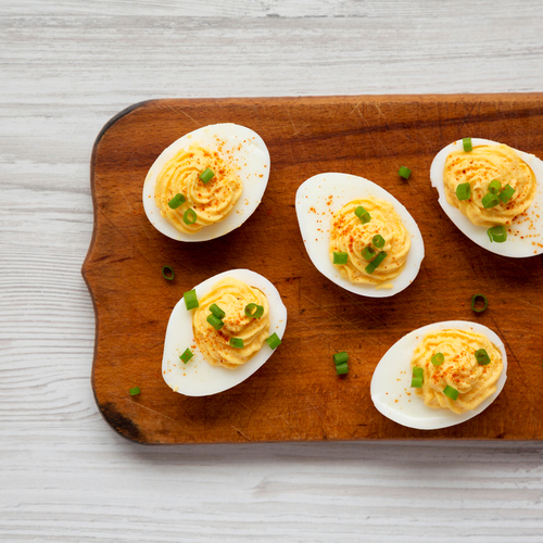 Homemade Deviled Eggs with Chives on a rustic wooden board.